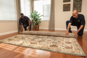 ServiceMaster Technicians Rolling a Rug
