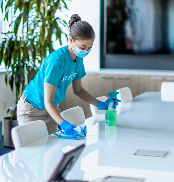 Woman cleaning an office conference table with a green cleaning product